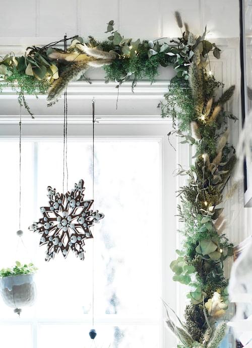 I köksfönstret hänger pepparkaksstjärnor och en växtgirlang med ljusslinga virad runt. Hemgjorda dekorationer som sprider väldoft.