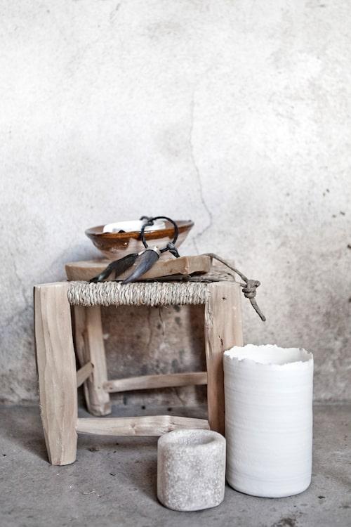 Grovhugget trä mot hård betong. Den vita keramiklyktan är drejad i porslinslera av Kajsa Cramer.