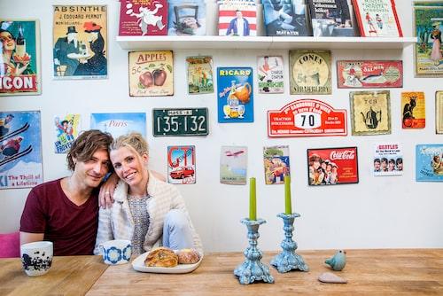 """Andreas med sin fru Lisa framför köksväggen som de fyllt med dekorativa emaljskyltar inhandlade på de återkommande familjesemestrarna i Sydfrankrike. """"Köket är jag väldigt nöjd med och här trivs jag bra. Och så gillar jag kökssoffan som gör att man kan sitta ett helt fotbollslag runt matbordetom man vill."""""""