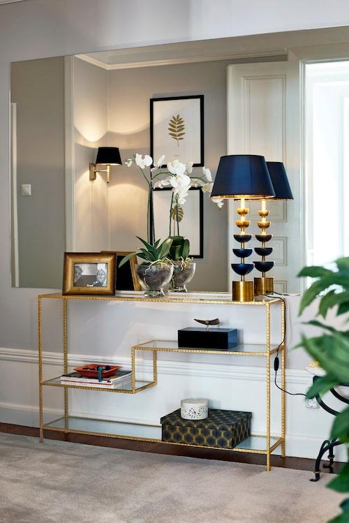 Gyllene detaljer sätter guldkant på hallen. Sideboard, Frejas boning, bordslampa, Posh living och lampetter från Odhners Böhlmarks. En måttbeställd spegel är klistrad på väggen, vilket förstorar intrycket i hallen och bidrar med ökat ljus.