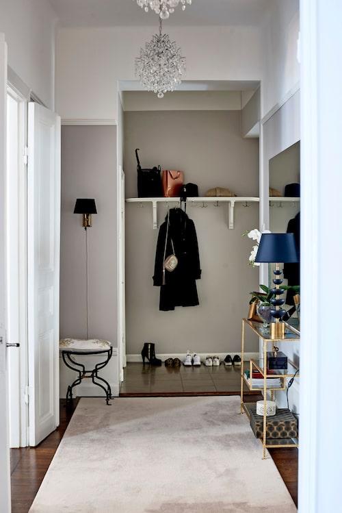 Snickeridetaljer som socklar, lister och den gamla hatthyllan i hallen är vitmålade i fin kontrast till de grå väggarna.