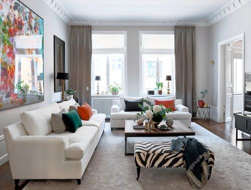 Tavlan till vänster har inspirerat till hemmets färgklickar. Här plockar kuddarna från Chamois och Louise Roe upp färgerna i det stora fotokonst-verket av Isabelle Menin. Vita soffor och zebramönstrad sittpuff från Slettvoll. Den generöst tilltagna mattan ligger som en bricka under soffgruppen, vilket ger ett välinrett och välkomnande intryck. Notera även gardinhängningen i fönstrens ytterkant, och ända från taket – ett sätt att få fönstren att kännas större.