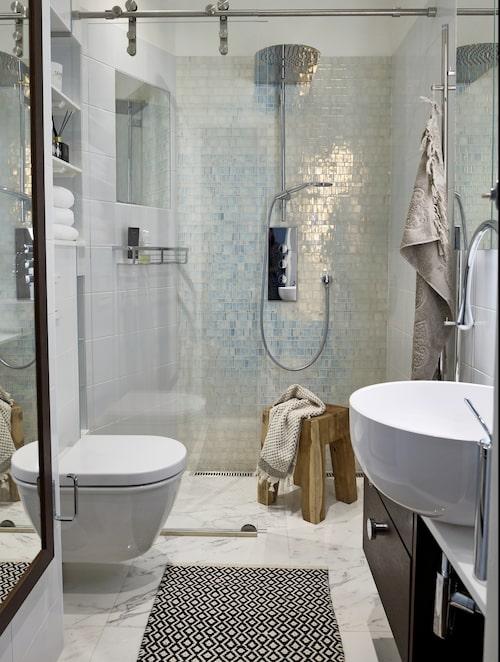 Badrummet är ganska litet så material och färger är valda för att få det att kännas rymligare. Detaljer i trä skänker värme åt den i övrigt kalla färgskalan med glasmosaik från Italien och rostfritt stål. Träpall från Muubs och handdukar, Craft collective.