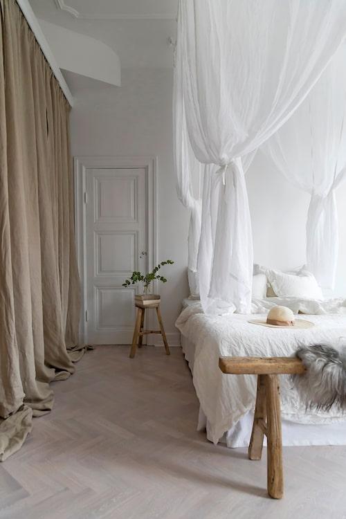 I det drömlika sovrummet hänger en baldakin från Ellos över sängen. Vid fotändan står en träbänk från Snowdrops Copenhagen.Golven är original fiskbensparkett som vitpigmenterats.