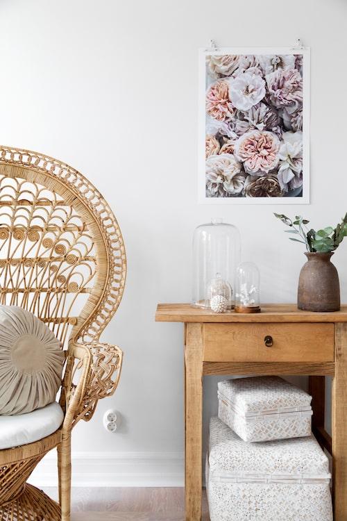 Ett vintagebord i trä från Soluppgången och en påfågelsstol i rotting från Modesto ger en mysig stämning i sovrummet. På bordet samlar Denice vackra detaljer under glaskupor. Förvaringsboxar från PB home.
