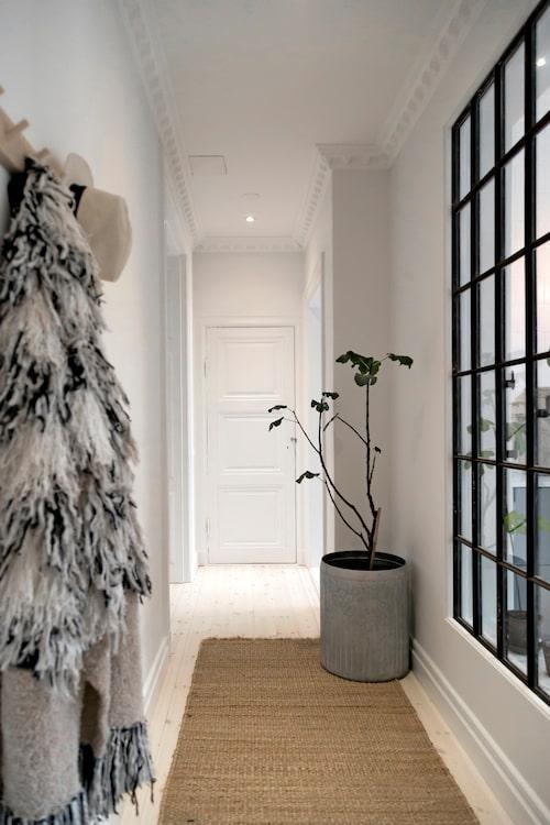 Hallen får in ljus genom det extra fönstret som byggdes in i väggen mot köket. Matta i beige sisal från Day home, och kruka i zink med Denices favoritväxt fikon.