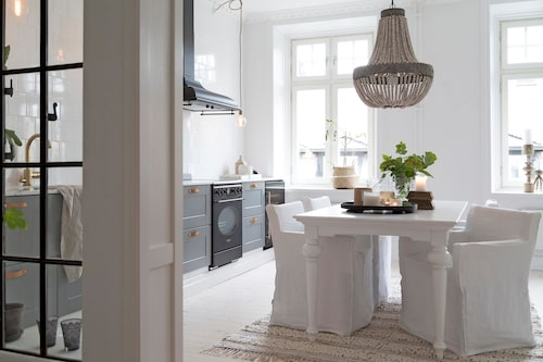 När man stiger in i lägenheten möts man av matplatsen. Matbordet kommer från Trademax, stolar Nils från Ikea med klädsel i linne från Bemz. Matta, taklampa, ljusstakar och vas kommer från Soluppgången.