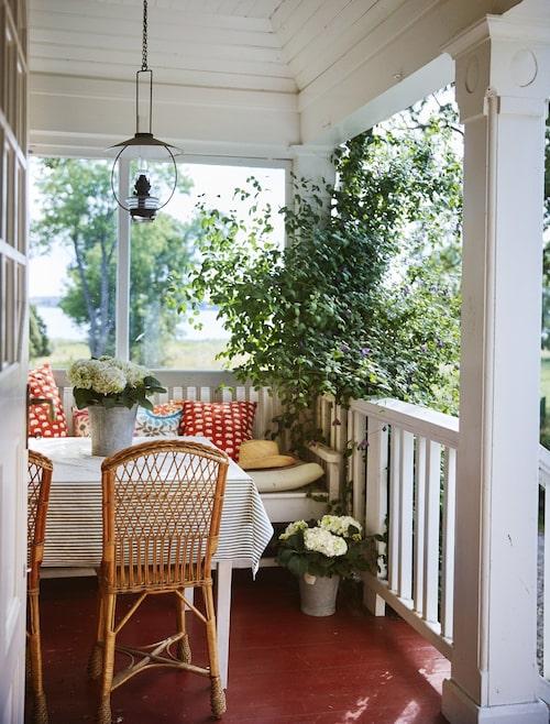 Ljuset silar vackert genom grönskan och fjärden glittrar. På den vackra verandan sitter familjen gärna och äter både frukost och middag.