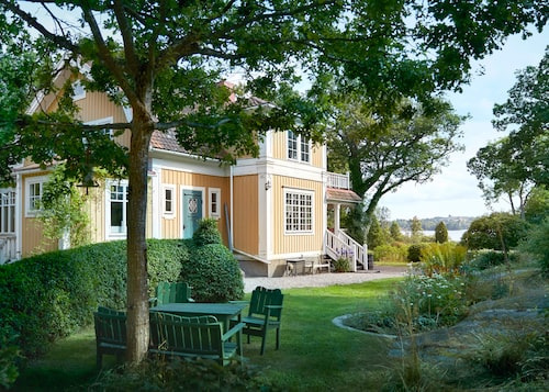 Huset sett från norr. Utemöbel i trivsamt grönt intill en av de välklippta ligusterhäckarna som finns på tomten.