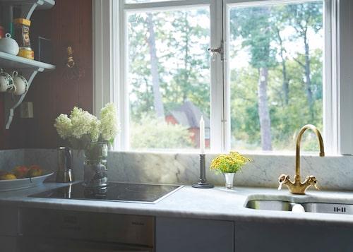 Vilsam vy vid disken. Ljus marmor mot roströda väggar i trivsamma köket.