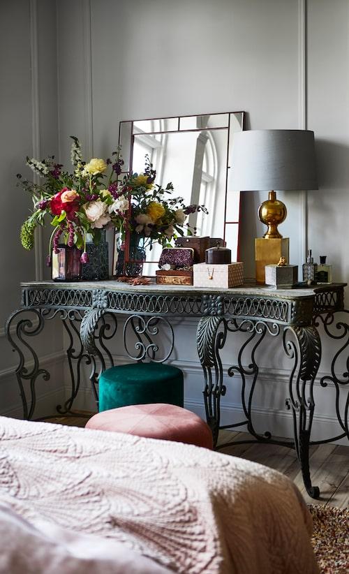 Antikt sidobord i gjutjärn, auktionsfynd, grön sammetspuff, 399 kr, Åhléns, rosa sittpuff Circus, 3400 kr, Asplund. Spegel från Svensk tenn, 9 800 kr.