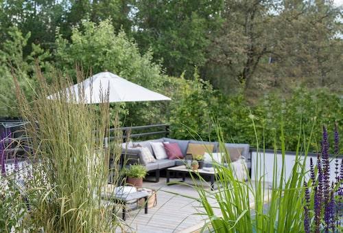 Från den låga vita muren reser sig växter som en skyddande barriär mot insyn. Loungesoffa och parasoll, privata Parasoll utemobler.