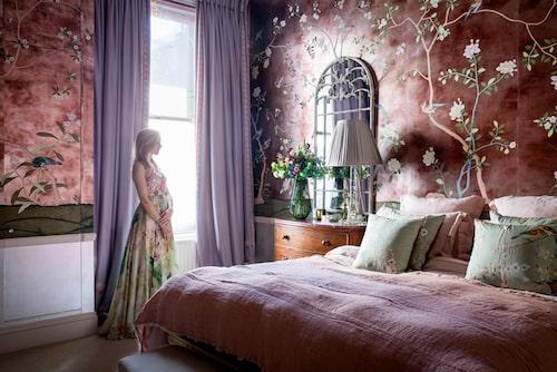 """""""I skymningen skimrar väggarna som antiksilver och gör rummet till det ljuvligaste i världen."""" Tapeten heter Badminton, handmålad från de Gournay. Pläd och linnelakan, The Conran shop, sidenkuddar, deGournay. Byrån med marmorskiva minns Hannah att hennes pappa köpte i en lumpbod och renoverade, när hon var liten. Hennes klänning är från Jenny Packham, men sydd i siden från deGournay som även gör tyger och, på senare år, möbler. Lampa, Guinevere, vas, India Jane, spegel, The French Bedroom Company."""