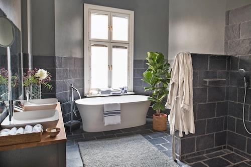 Mörka skifferplattor ligger på golvet och får klättra upp på väggarna. Dessutom är duschdelen klädd i skiffern Spanish black slate från Farrow & Ball. Dold bakom duschväggen, en vägghängd toalett. Rottingkorgar, Walles & Walles, bukett och fikus i korg, Floristkompaniet. Handduk över badkarskant, och morgonrock, båda Linum.