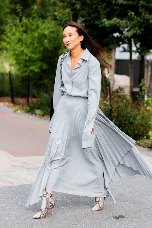 En feminin, plisserad kjol tillsammans med en maskulin skjorta med något längre skjortärm skapar en elegant balans mellan två stilar.