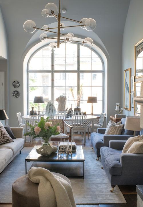 Vardagsrum med ljus och rymd, och stenväggar som effektivt skärmar av mot ljud utifrån. Taklampa från Eichholtz, soffa och puff från Mio, och filt, Oscar&Clothilde. Kuddar i soffan, H&M Home och Bohem. Matta, Bohem. Soffbord med stenskiva från Posh living. Hand från Oscar&Clothilde. Matbordet och stolarna omklädda i linnetyg hängde med från ett tidigare husköp.