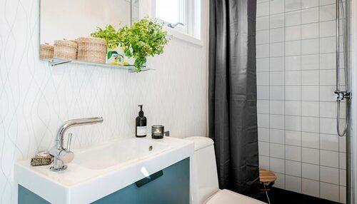 I badrummet ryms dusch, tvättställ och toalett.