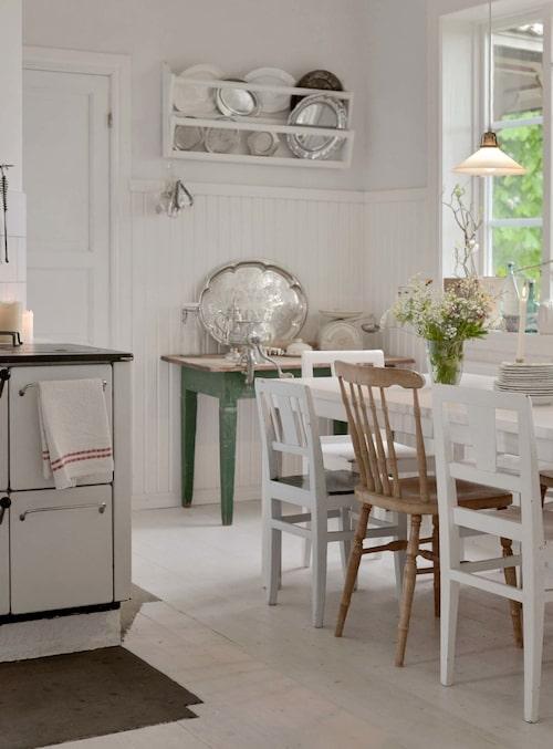"""Pärlsponten i köket är ny och kommer från Skirö träförädling. Golven är däremot original befriade från mångårigt täcke av plastmatta och ytbehandlade på """"hemligt"""" sätt. Tallrikshyllan räddades från att bli slängd på tippen, och bordet under hittades i ett uthus. Stolarna kommer från gamla skolan i Lönneberga och är inropade på auktion. Det mesta av kökets pryttlar är köpt på loppis."""