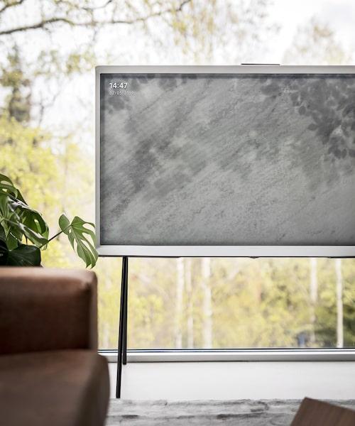 Tv:n har stilrena svarta ben att stå på, om man vill få in mer luft i rummet och inte behöva ha en tv-bänk.