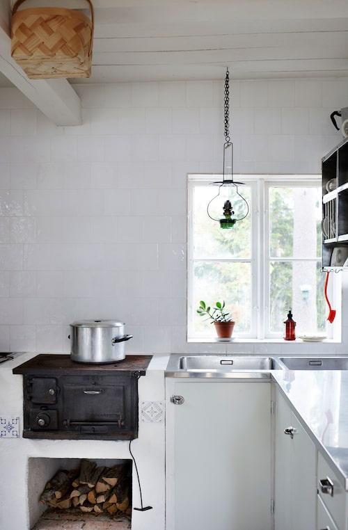 Kökets väggar är klädda med skimrande handslagna kaklet Prinsen köpta på Gysinge.