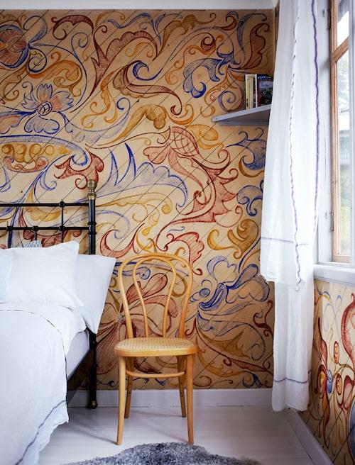 Gästrummet målades 1926–27 av byggherre Carl de Vals dotter. Om man tittar noga ser man djur inmålade i det färgstarka -kurbitsinspirerade mönstret. Fin rottingstol som sängbord. Säng och sängkläder Ikea. Lammskinn Gotlamm.