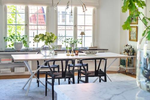 De djupa 20-talsfönstren är riktiga smycken, och ljusinsläppet i matsalen är magnifikt. Bord, No early birds, Y-stolar av Wegner. På bordet vasen Pallo av Carina Seth Andersson, mässingsljusstakar Nappula, Iittala.