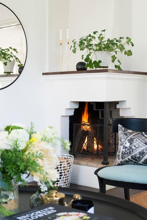 Öppna spisen tronar i ena hörnet i det ljusa vardagsrummet. Vedkorg, Asplund, omklädd antik stol av Made by Märtha.