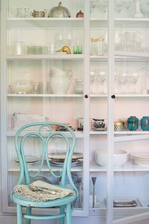 Vitrinskåpet i köket, från Lindebjerg design, är fullt av vackra glas, karaffer, anitikviteter och loppisfynd. Stolen är köpt i antikaffär.