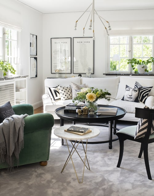 Vardagsrummets ombonade mix med pösiga sittmöbler, grafiska detaljer och moderna lampor och konst.