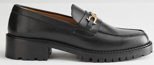 Höstsäkra loafers från & Other Stories med grov sula och elegant kedjedetalj. Klicka på bilden och kom direkt till skorna.