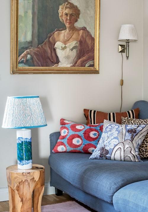 I tv-rummet hänger ett porträtt av Cathys gammelmormor. Soffan är fylld av kuddar och myskänsla. Lampfoten på stubben av Olle Alberius, och skärmen från Pooky lighting i England.