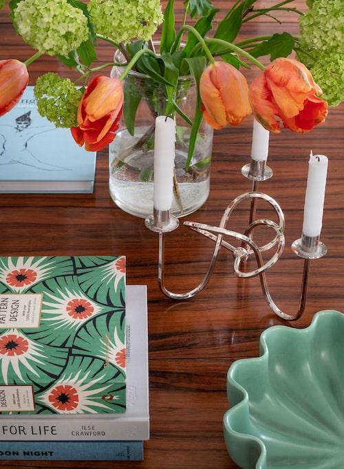 På bordet av palisander stå klassiska ljusstaken Vänskapsknuten, formgiven av Josef Frank 1938.