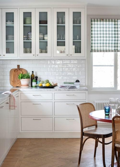 I huset är färgvalet ljust, men vitt är det bara i det platsbyggda köket. En fin detalj är att skåpen är målade inuti i en duvblå färg. Hissgardiner i tyg med klassisk gripsholmsruta återfinns i flera rum.