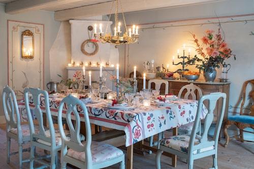 """Takkronan i matsalen är nytillverkad i empirestil. De ärvda stolarna har olika tyger på sitsarna. """"Varianter som vi provat att klä dem med, och sen har proverna blivit kvar."""" Skänken följde med huset."""