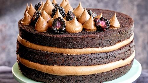 Garnera chokladtårtan med kanderade mandlar och björnbär.
