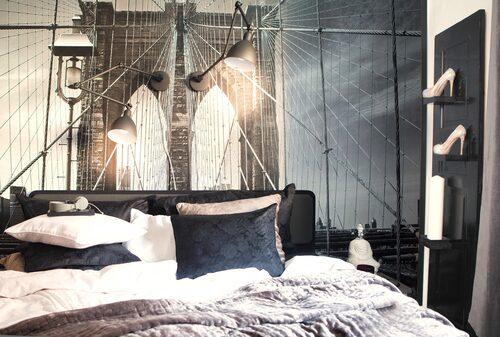 Brooklyn bridge har utifrån ett foto förvandlats till tapet av Photowall. Vägglamporna kommer från By Rydéns. Hyllan bredvid sängen är specialtillverkad av lovsjologhouse.se efter en idé av Jimmy Schönning, som inrett lägenheten ihop med Sarah. Kuddar och påslakan från Ateljé alt.