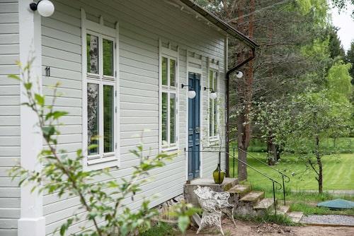 Missionshuset hade stått tomt i flera år när det hamnade i nuvarande ägarnas händer. De har målat huset i dess ursprungliga sandgrå färg. Utomhusbelysning från Nacka byggnadsvård. Ormbunkssoffan är köpt på Blocket.