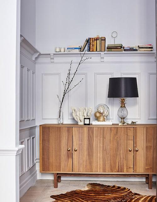 Hallens panel är nytillverkad i gammal stil och har en liten hylla för smått och dekorativt. Sideboard i valnöt, Ikea Stockholm. Lampfot och skinnmatta, Zara home, skärm från Bohem. Glaskupa, Granit.