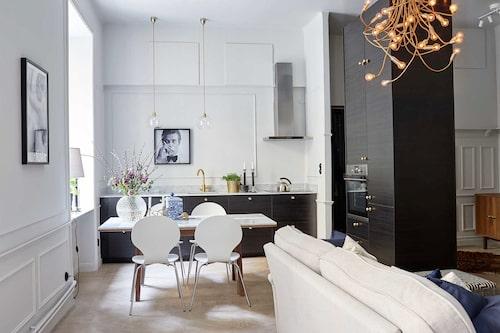 """Sophia har skapat """"vardagsrumskänsla"""" i köket med hjälp av belysningval och knoppar. Kök och matbord från Ikea, med blanka marmorskivor från Diapol. Kran, Tapwell, lampor, Rowan. Stolar, Mio. Fotokonst med James Bond (Roger Moore), köpt på nätet."""