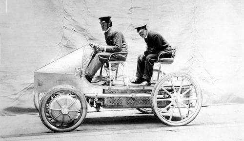 Ferdinand Porsche vid ratten i en av sina eldrivna tävlingsbilar. Porsche har byggt en strömlinjeformad front. Mannen baktill är en medarbetare, Karl Paulal, på Lohner-fabriken i Wien där Porsche arbetade. Bilden är tagen den 23 januari år 1900.