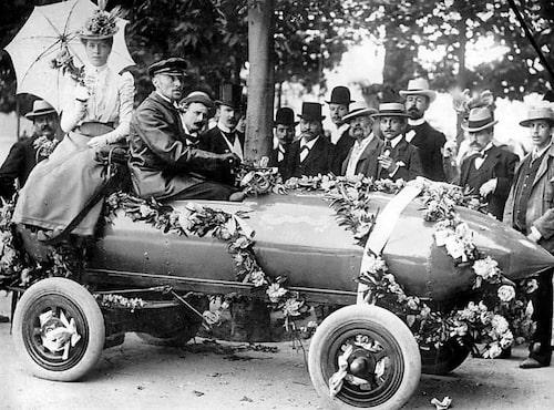 Världens snabbaste man – belgaren Camille Jenatzy. Han sprängde 100 km/h-vallen med sin elektriska bil. Här förmodligen fotograferad höljd i blommor när han slog rekordet. Vem är damen bakom Jenatzy?