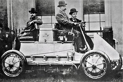 Ferdinand Porsche konstruerade elbilar i sin ungdom. Här i framsätet bredvid chauffören som möjligen är hans arbetsgivare Jacob Lohner. Bilen har fyra elmotorer. Man ser dem tydligt i hjulens nav. Detta kan alltså vara världens första fyrhjulsdrivna bil. Efter ett besök i en fransk bilfabrik slutade Porsche tro på elbilens framtid.