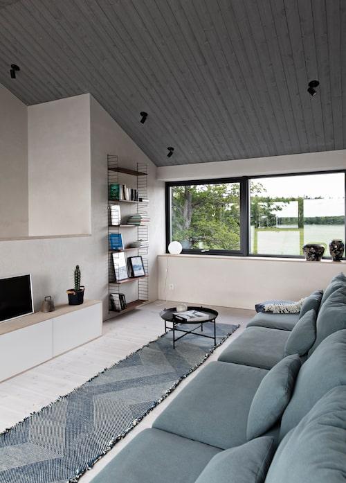 På övervåningen finns det stora tv-rummet, med utsikt över havet. Och en gråblå soffa som rymmer hela familjen. Mattan kommer från kusiner.dk och bordet från Ikea. Skåpet har Elias själv byggt.