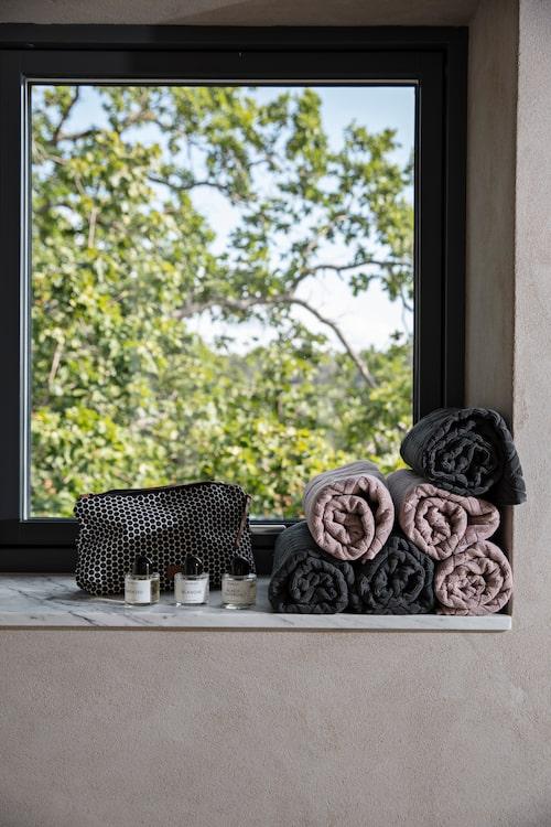 Snyggt rullade handdukar från Mette Ditmer ligger nära till hands i badrumsfönstret.
