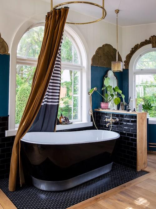 Sammetsgardinerna från Johannas farmor används till våningens alla fönster och har i badrummet fodrats med ett duschdraperi från Ikea. Den runda duschstången i mässing är köpt på engelska The bathroom look och badkaret kommer från Neptun i Helsingborg.