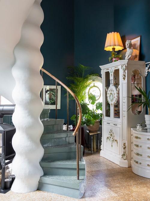 Spiraltrappans stänkmålade steg möter nedervåningens terrazzogolv. Båda är husets ursprungliga. Det kitschiga vitrinskåpet är köpt hos antikhandeln Eufemia nött & nytt på Öland.