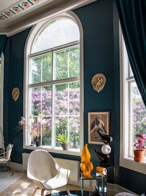 Nedervåningens stora fönster vittnar om tiden då Palmhuset användes som orangeri. Fåtöljen kommer från Johanson design där Johanna arbetar som mönsterkonstruktör. Tuppskulptur från Jotex.
