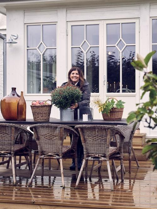 Maria gör den nybyggda altanen höstfin. Fönstren byttes vid renoveringen ut till nya i gammal stil.