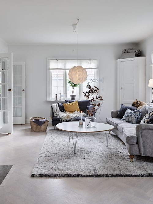 Det mysiga vardagsrummet gillas av franska bulldogen Ture. Hörnskåpet är från Blocket och platsbyggt av Martin. Taklampa, Le Klint.