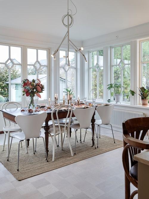Matplatsen får fantastiskt ljus genom glasverandans vackra fönster. Runt matbordet samsas stolklassiker av Arne Jacobsen och Thonet. I taket hänger Jonas Bohlins  lampa Kvist. Maria har också en särskild förkärlek för engelskt porslin och mässingsljusstakar.